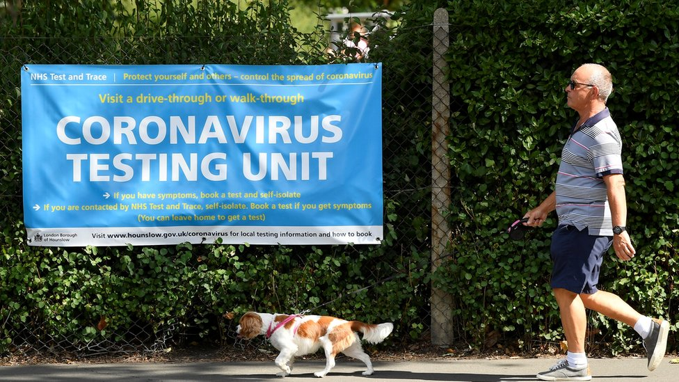 A man walks his dog past a poster promoting the coronavirus disease (COVID-19) testing at local mobile test centres, in Hounslow