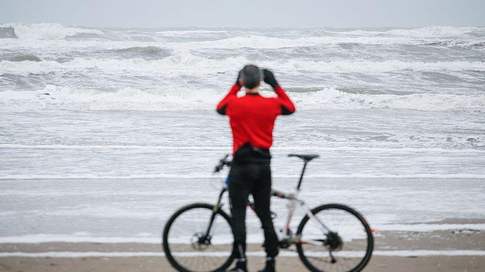 Hombre fotografiando una playa en Países Bajos.