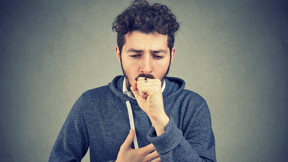 Hombre joven tosiendo.