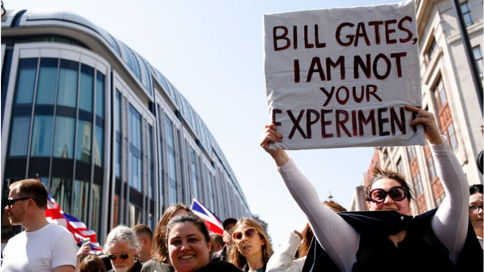 Woman holds sign about Bill gates at protest