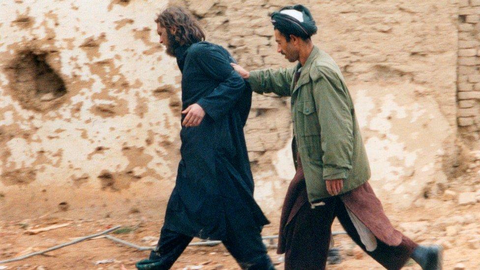 John Walker Lindh (izquierda), trasladado por un soldado de la Alianza del Norte en Afganistán en 2001.