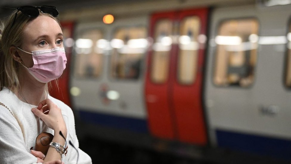 Woman in a mask waiting for a train