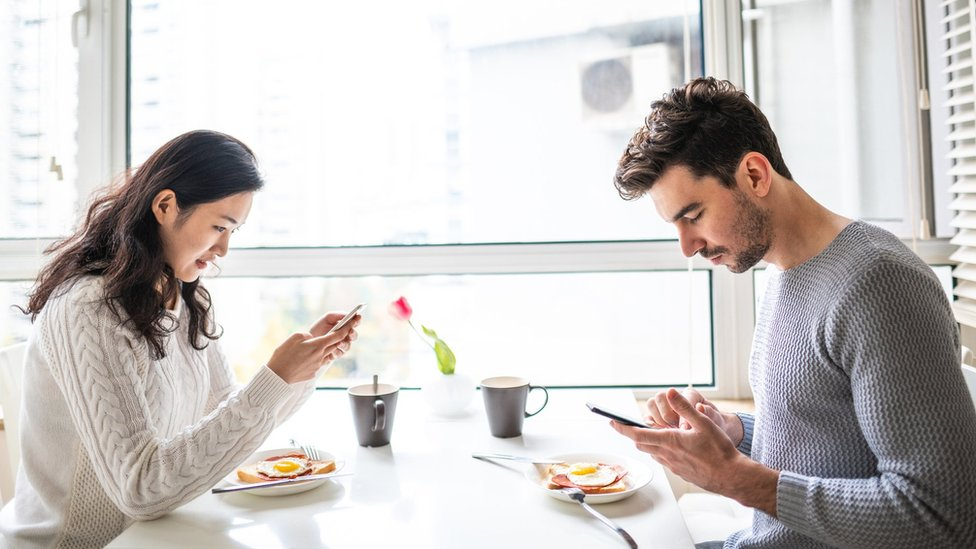 Couple drink tea as they look at their phones