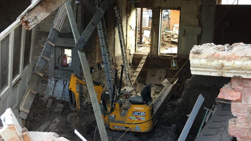JCB digger inside collapsed house