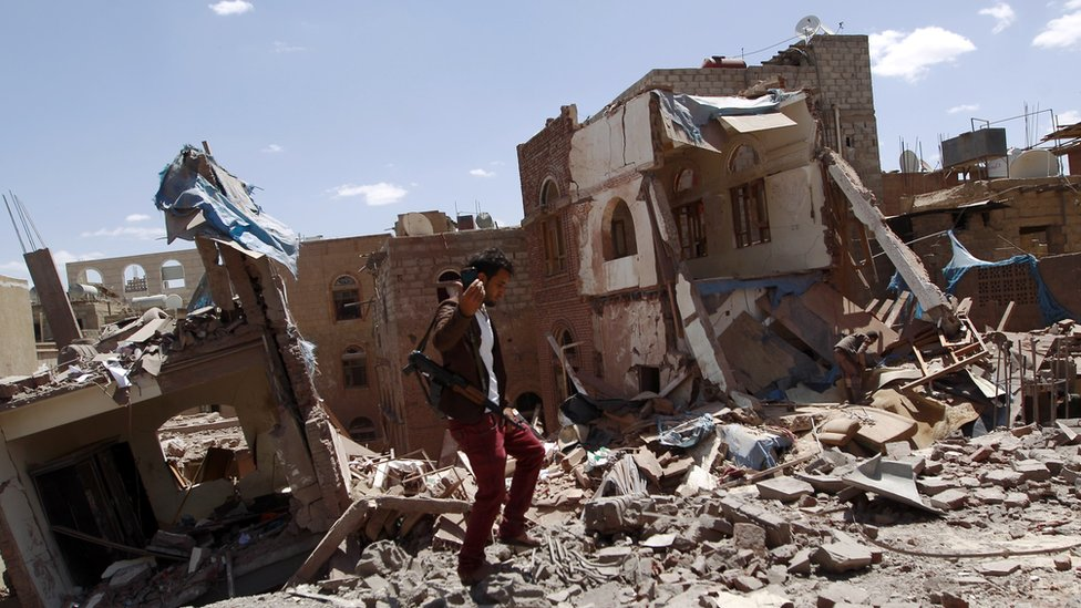 An armed Yemeni man on the ruins of buildings destroyed in an air strike by the Saudi-led coalition in Sanaa