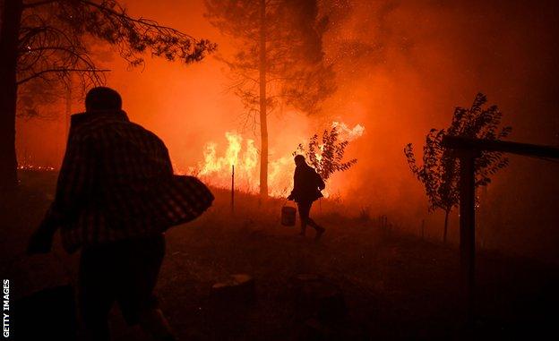 Seljani nose kofe sa vodom da bi pokušali da ugase vatru blizu svojih domova u Makau, južno od Tondele, u julu 2019. godine