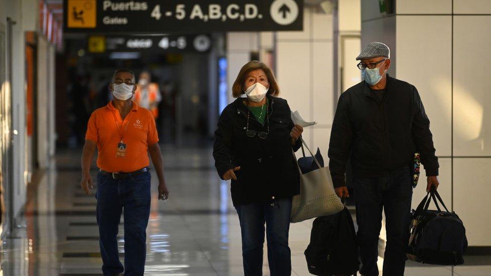 Personas con mascarillas en el aeropuerto de El Salvador.