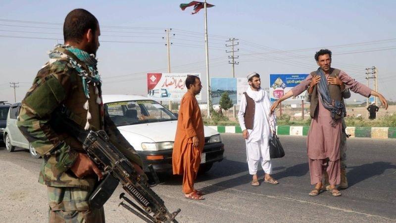 جنود أفغان يفتشون رجلا عند نقطة تفتيش في ولاية هرات