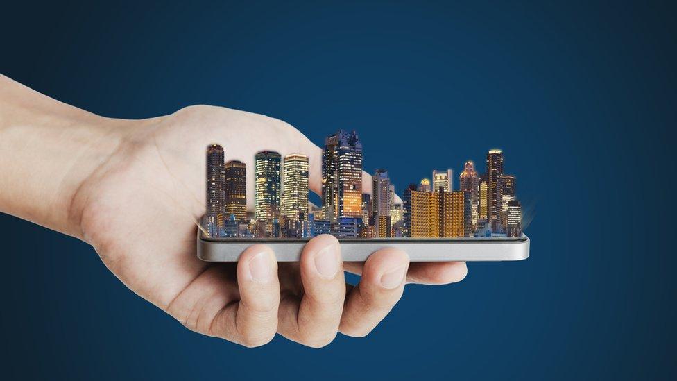 Mano y celular con edificios