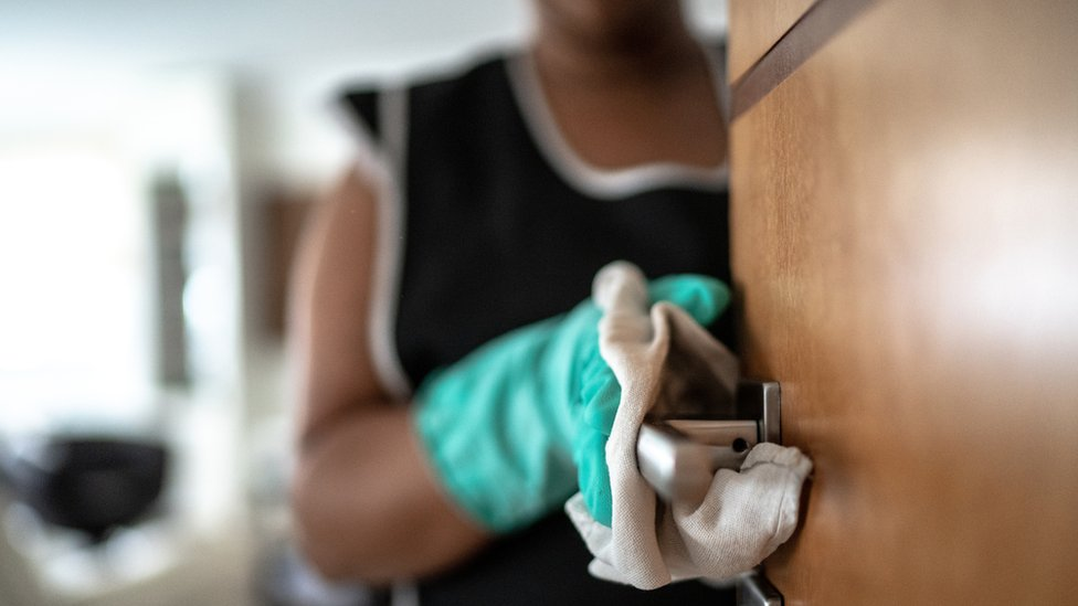 Mujer limpia el picaporte de una puerta