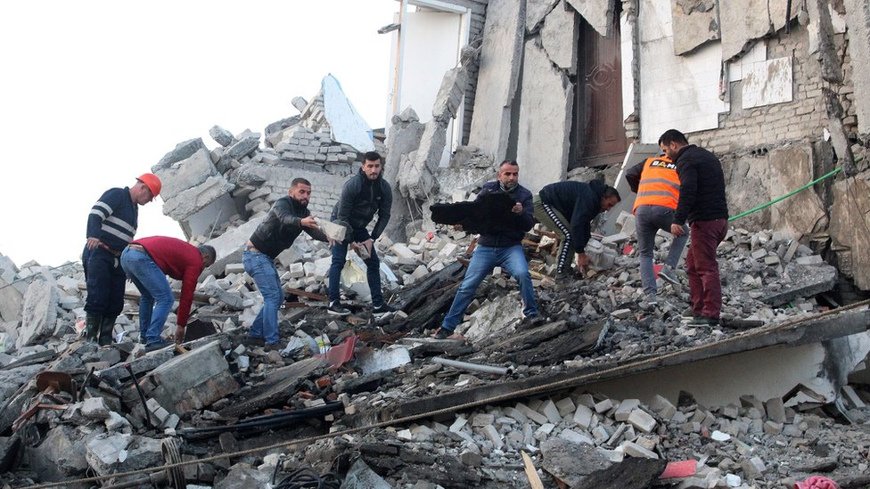 People stand on a collapsed building and move rubble