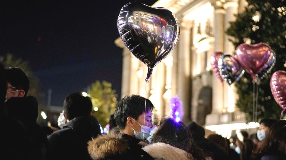 A couple kissing in the street holding a balloon