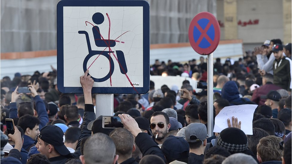 Protesters put a red cross through a wheelchair access sign in Algiers, Algeria