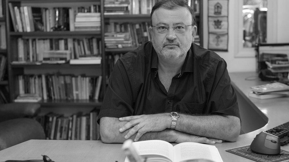 Chrstian Dunker sentado en una mesa con una estantería llena de libros detrás