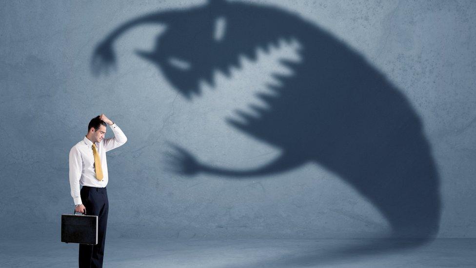 Hombre delante de la sombra de un monstruo.