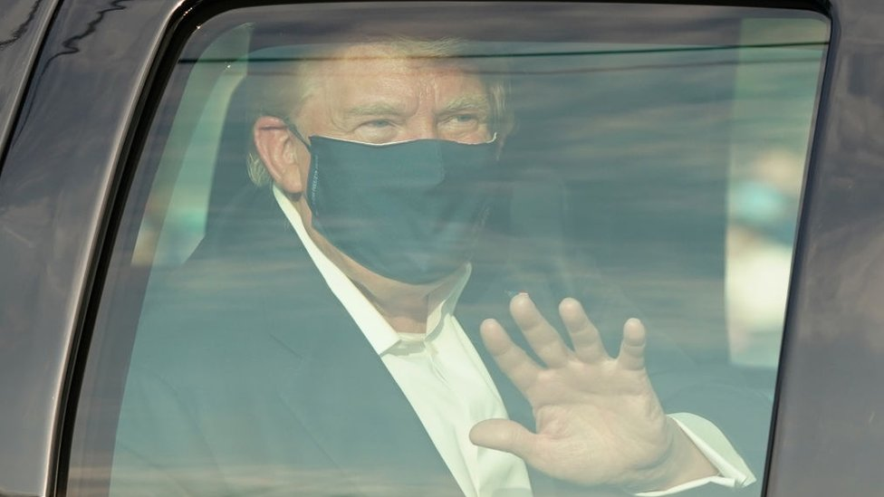 El presidente de Estados Unidos, Donald Trump, con una mascarilla y saludando con la mano desde un auto con la ventana cerrada