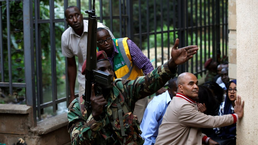 A member of the security forces gestures as people take cover at the scene where explosions and gunshots were heard at the Dusit hotel compound, in Nairobi, Kenya