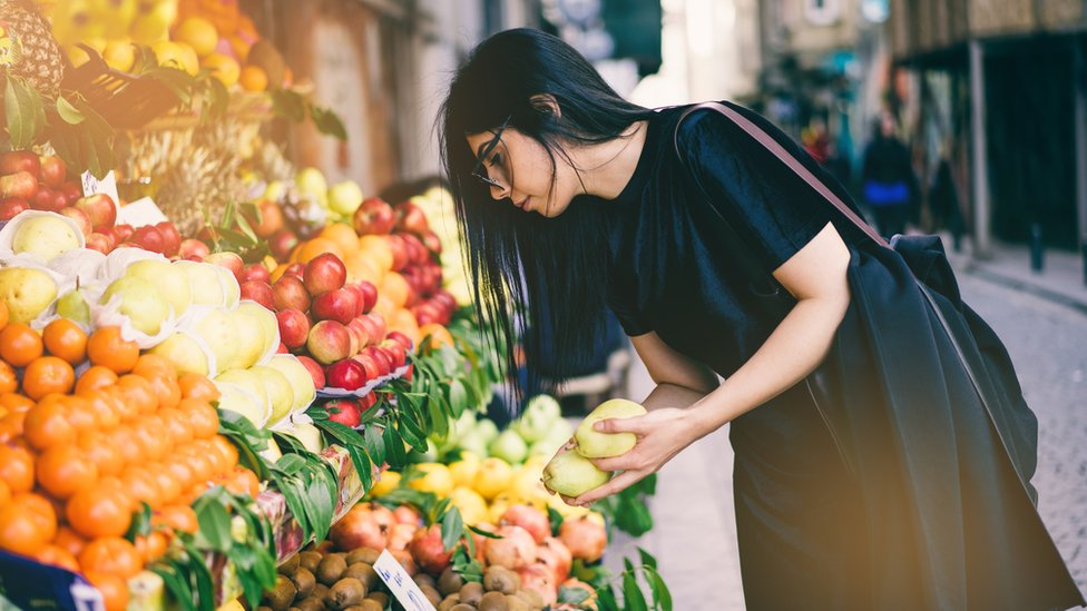 Woman Buying Fruits on Street Market - stock photo