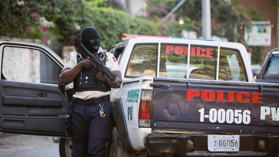 Haitian police officer holding an automatic firearm next to his patrol vehicle in Petion-Ville, Haiti, Thursday, Jan 5, 2017