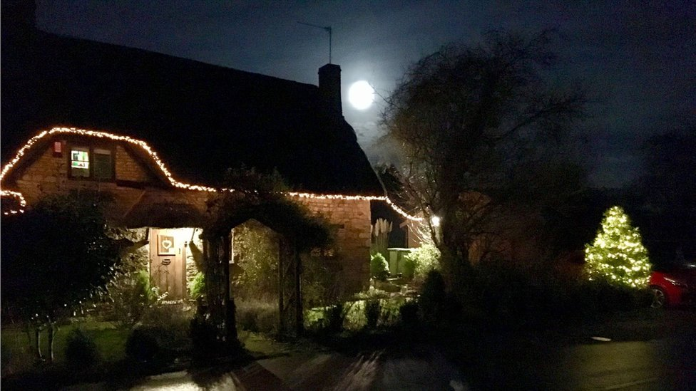 The supermoon between a house and tree appearing to be close to the ground