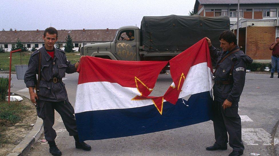Hombres sosteniendo una bandera yugoslava rota.