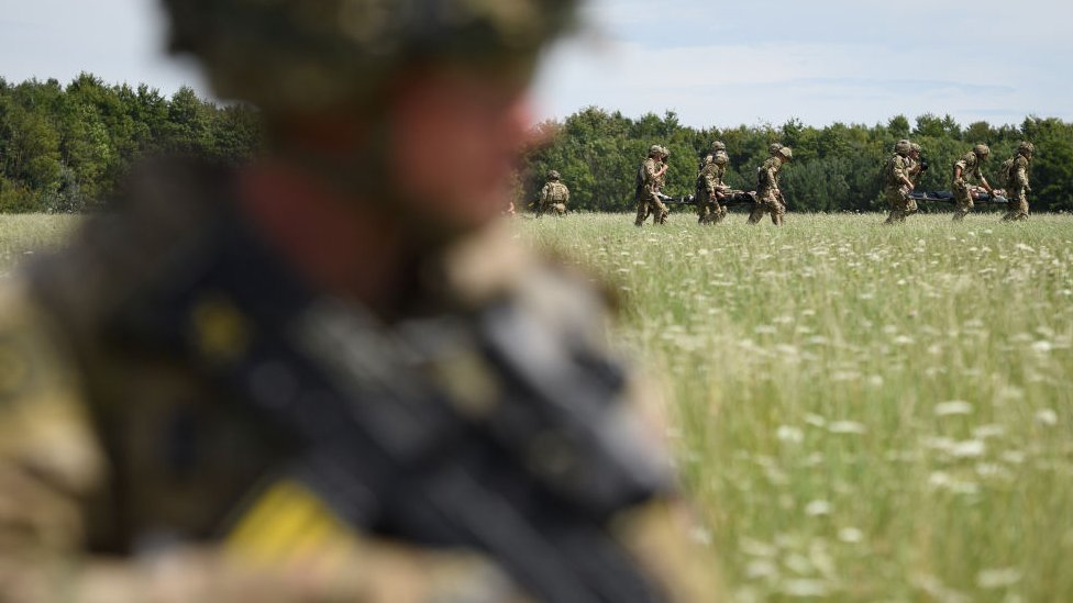 Private Patrick Rodgers of the Anglian Regiment, 2nd Battalion awaits the arrival of a Chinook helicopter for a medical evacuation during a military exercise on Salisbury Plains on July 23, 2020 near Warminster, England.
