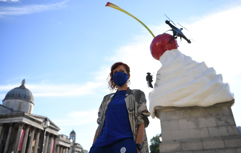 Artist Heather Phillipson stands in front of a sculpture depicting a whirl of cream with a cherry, fly and drone on top