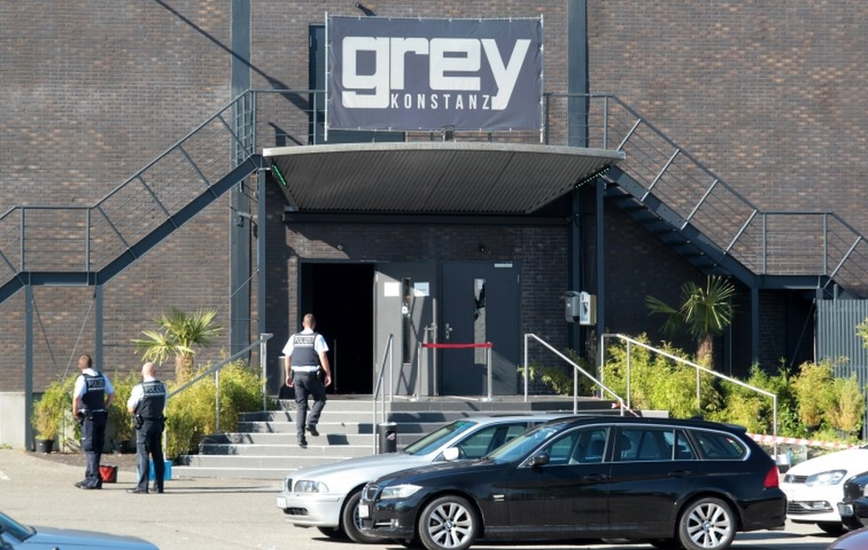 """Police officers stand at the door of the night club """"Grey"""" in Konstanz, Germany, on 30 July 2017. According to a police report, a 34-year-old man shot at several people inside the club in the early morning."""