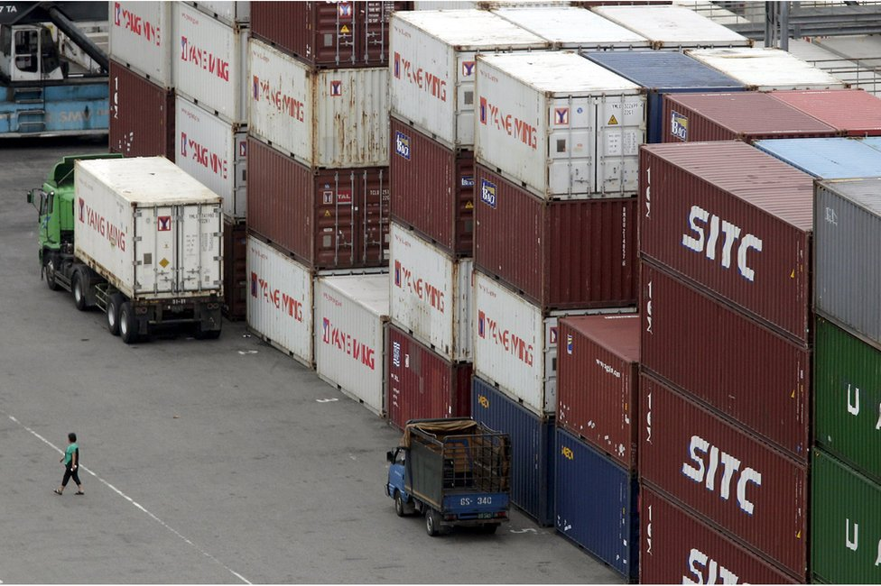 A person walks near containers at Keelung port, northern Taiwan, 30 October 2015