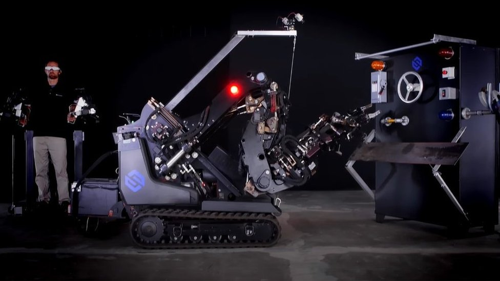 Man wearing exoskeleton operating large robot