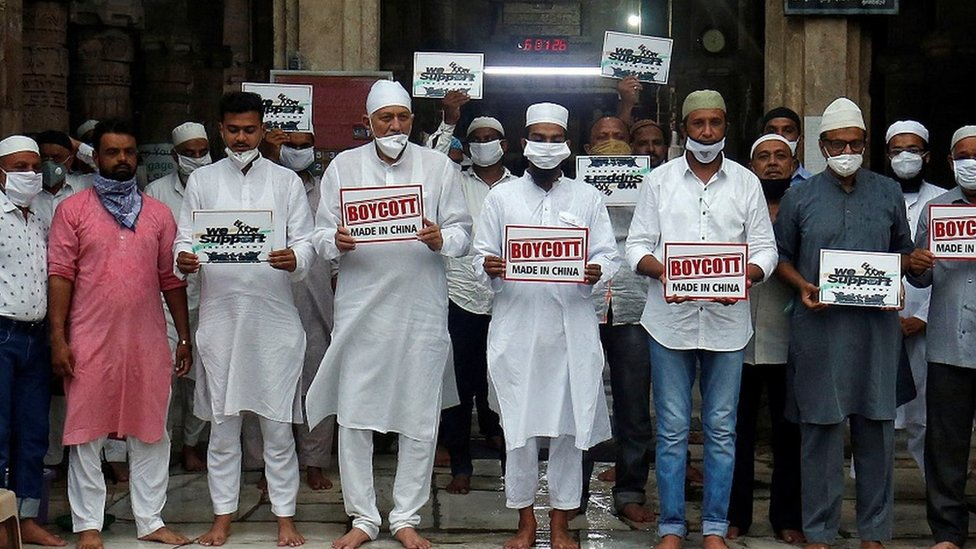 Muslims wearing protective face masks hold placards as they pay tribute to Indian army soldiers, who were killed in a border clash with Chinese troops in Ladakh region last month, and demand to boycott China-made products, after a prayer meeting at a mosque in Ahmedabad, India, July 3, 2020