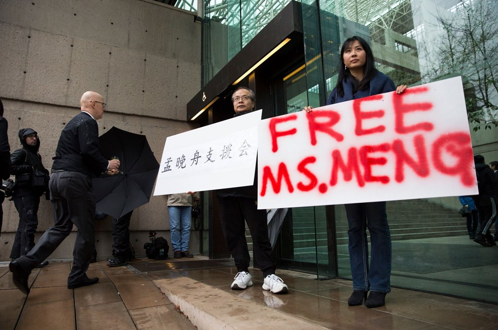 Robert Long (L) and Ada Yu hold signs in favor of Huawei Technologies Chief Financial Officer Meng Wanzhou outside her bail hearing at British Columbia Superior Courts following her December 1 arrest in Canada for extradition to the US, in Vancouver, British Columbia on December 11, 2018. (Photo by Jason Redmond / AFP)JASON REDMOND/AFP/Getty Images
