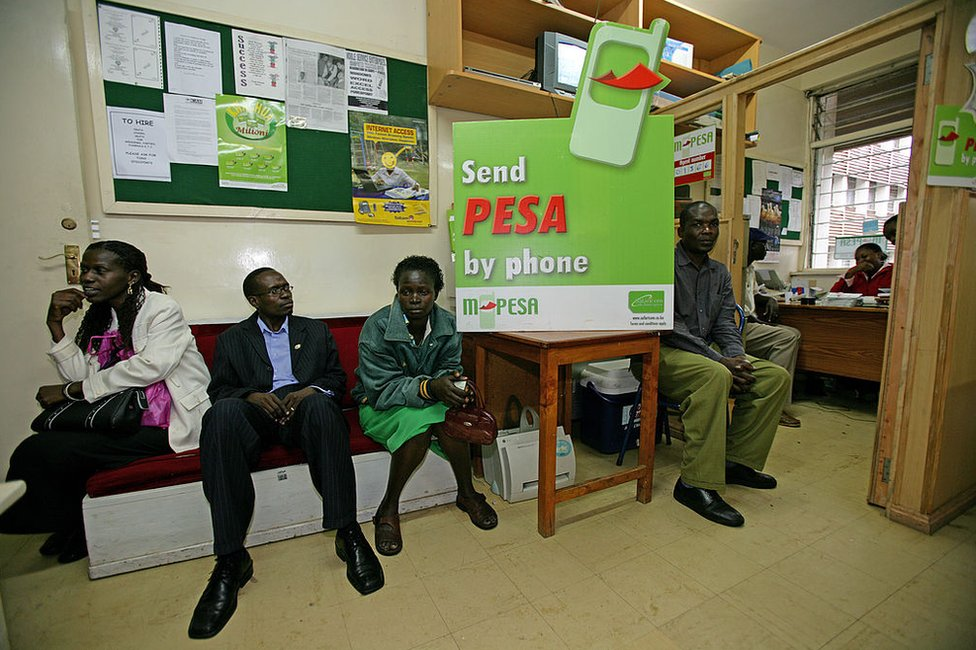 Customers wait in the office of an M-Pesa financial company office in Bungoma, Kenya