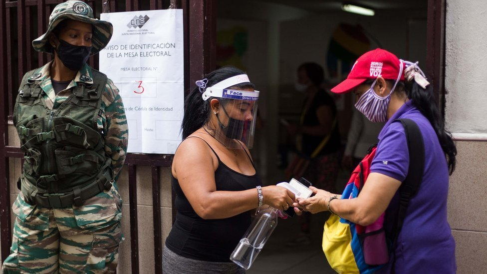Woman having hand sanitiser applied at an election registration station in Venezuela