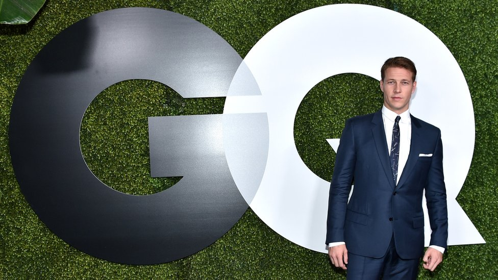 Man in front of GQ logo
