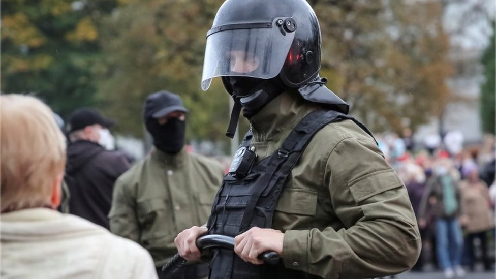 Law enforcement officer in black helmet and holding truncheon at a rally in Minsk (12 October)