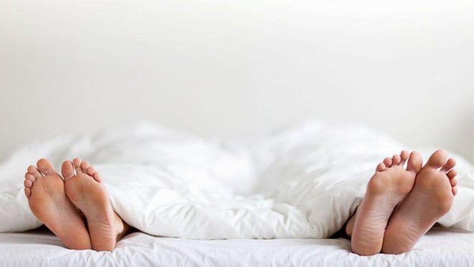 Una pareja en cama a la que solo se le ven los pies.
