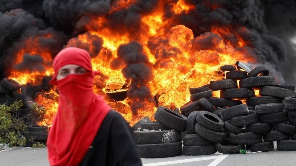 A protester stands in front of blazing tyres in Montegro