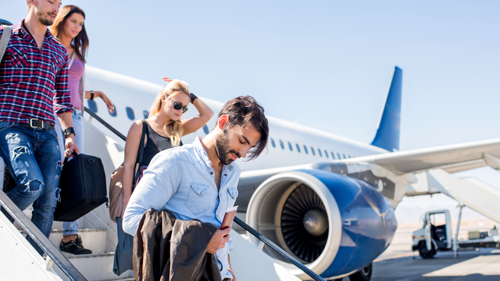 Jóvenes bajando de un avión