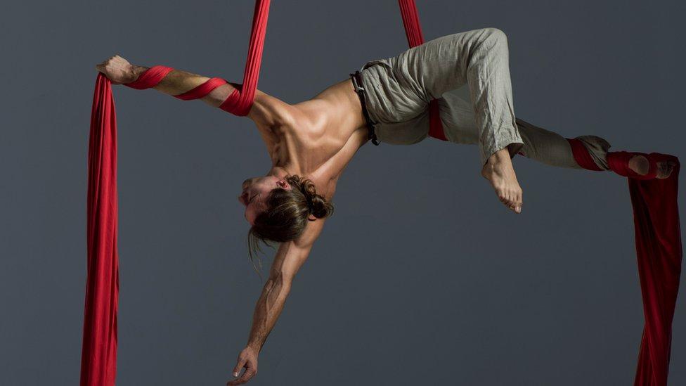 Persona haciendo ejercicio con una tela acrobática.