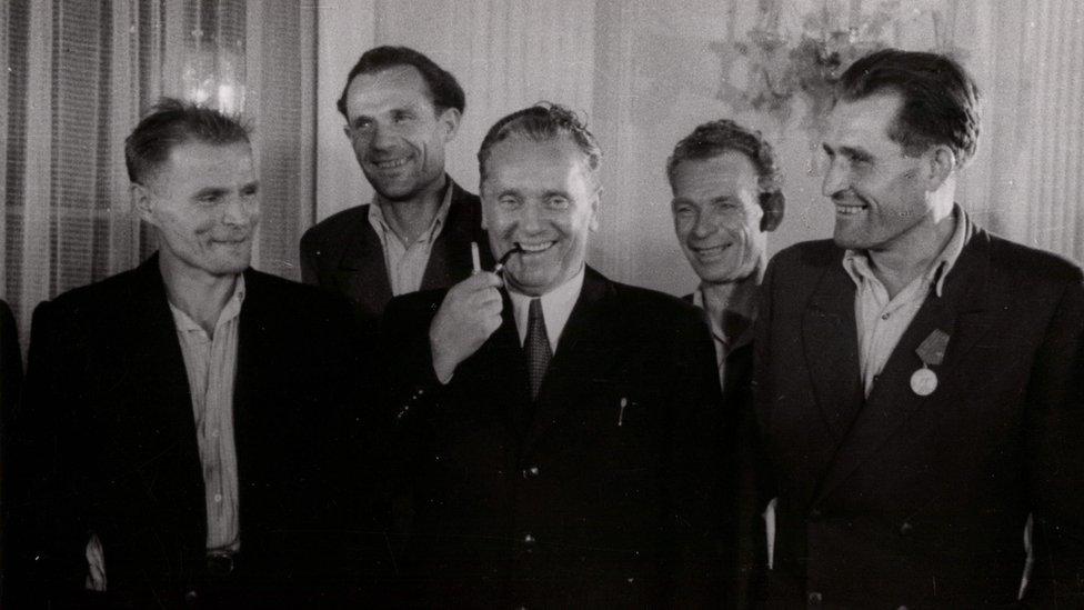 Tito u sredini puši lulu, oko njega okupljeni nasmejani radnici