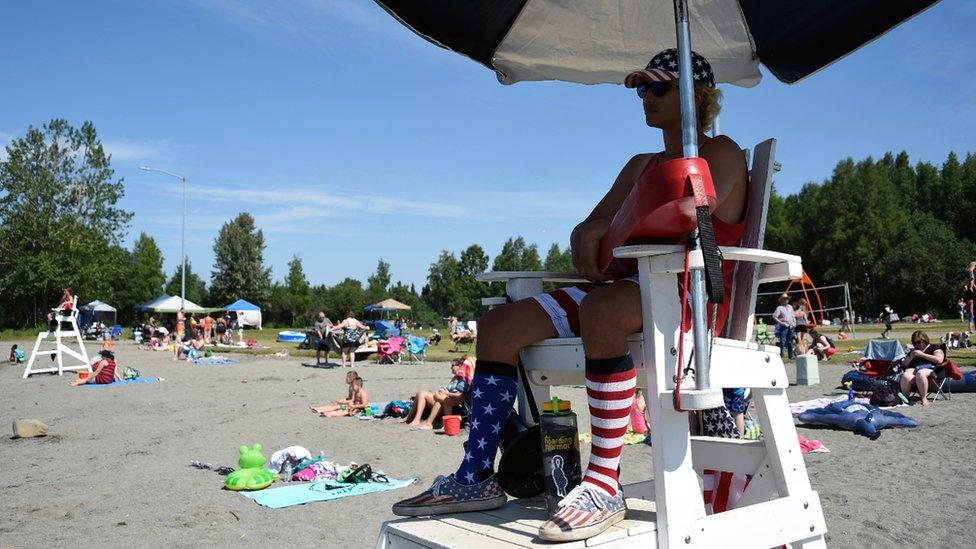 A lifeguard watches as people sunbathe at Jewel Lake, Anchorage. Photo: 4 July 2019