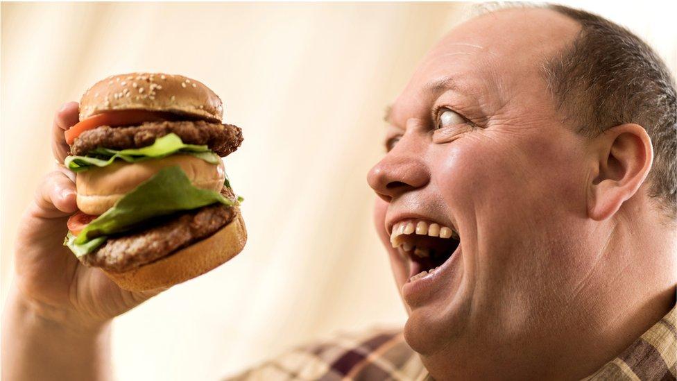 čovek jede hamburger