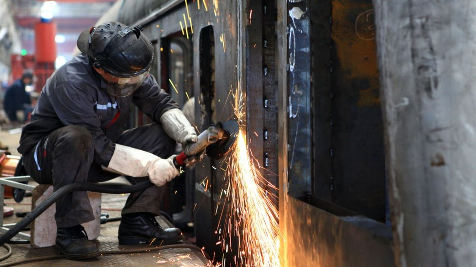 Chinese workers assembling new locomotive trains to be exported to Nigeria