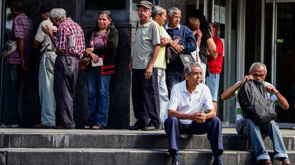 Adultos mayores venezolanos haciendo fila para cobrar su pensión.
