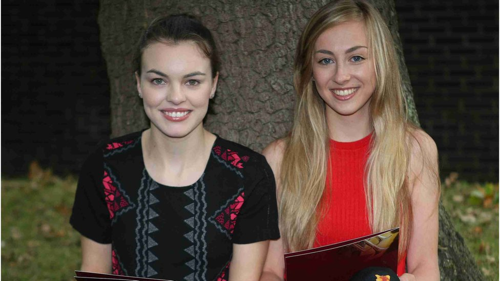 Victoria College pupils Elizabeth Brush and Jessica Sutton relaxing by a tree with their results