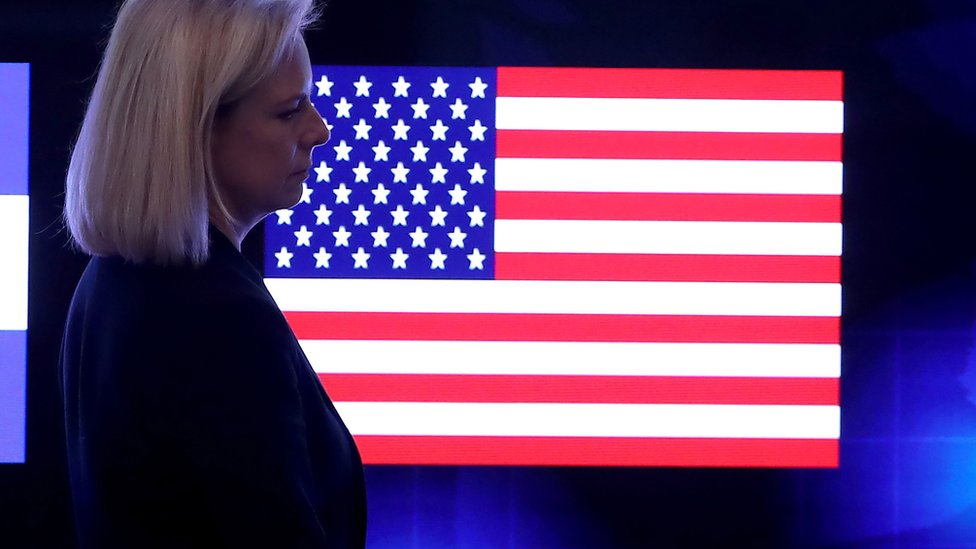 Nielsen in front of a US flag