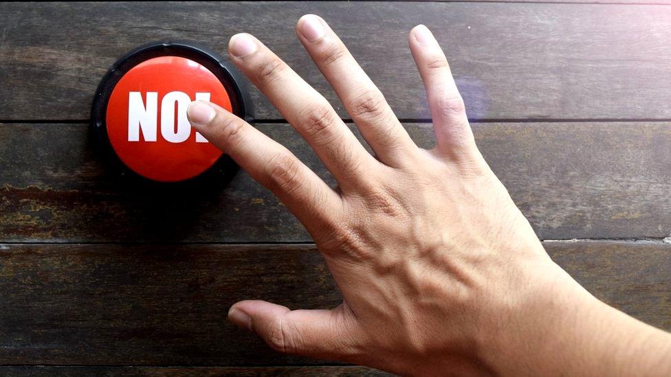 Mano a punto de tocar botón que dice No