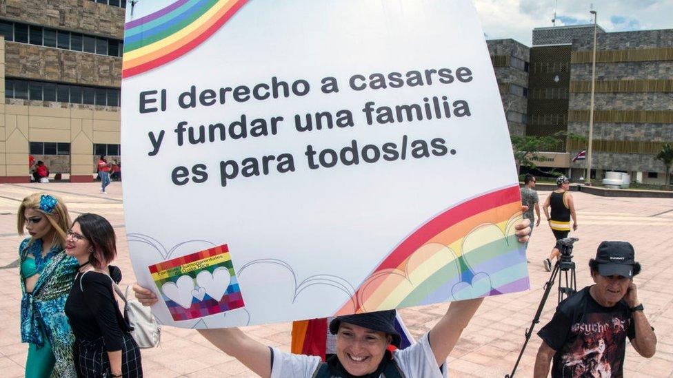 """Manifestante con letrero que dice: """"El derecho a casarse y fundar una familia es para todos/as""""."""