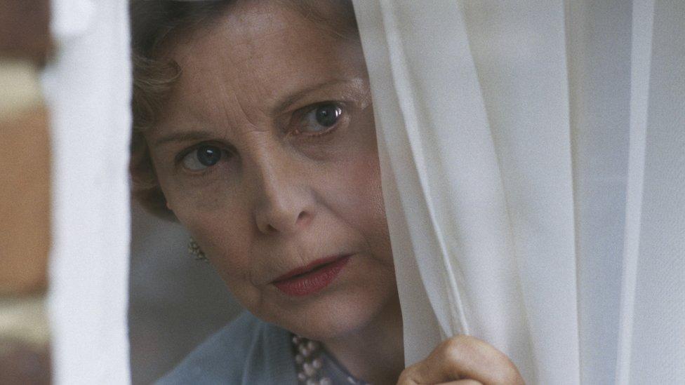 Žena gleda kroz prozor, drži zavesu